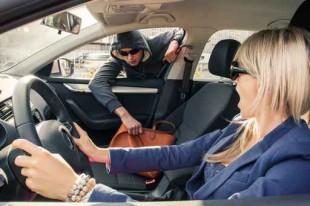 Thief brutally steals woman's handbag while she is driving a car